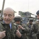 French Defence Minister Alain Juppé (L) visits French soldiers for Christmas at Forward Operating Base Tora at Surobi province on December 25, 2010. Around 113,000 international troops are in Afghanistan under US and NATO command to help keep Karzai's vulnerable government in power. AFP PHOTO/JOEL SAGET